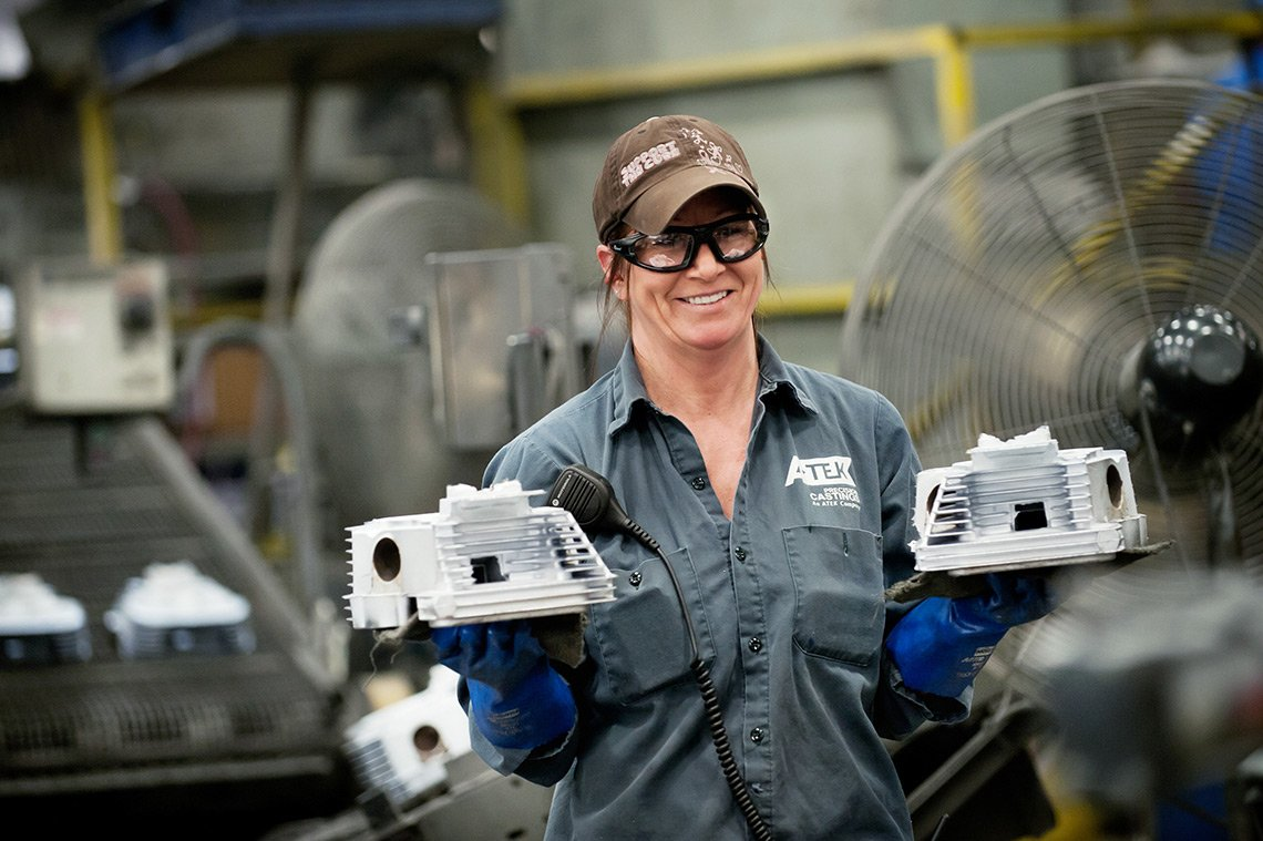 A woman holds two freshly made carburetors at Atek Precision Castings