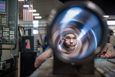 Industrial photograph of a worker inspecting a cylinder at Aggressive Hydraulics in Mpls MN