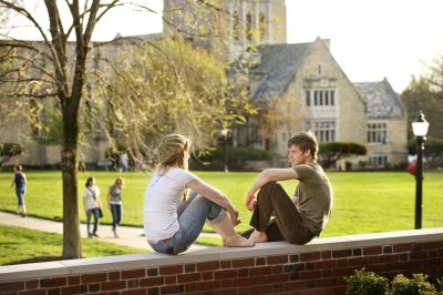 Two college students sitting on a wall talking at Grove City College in PA
