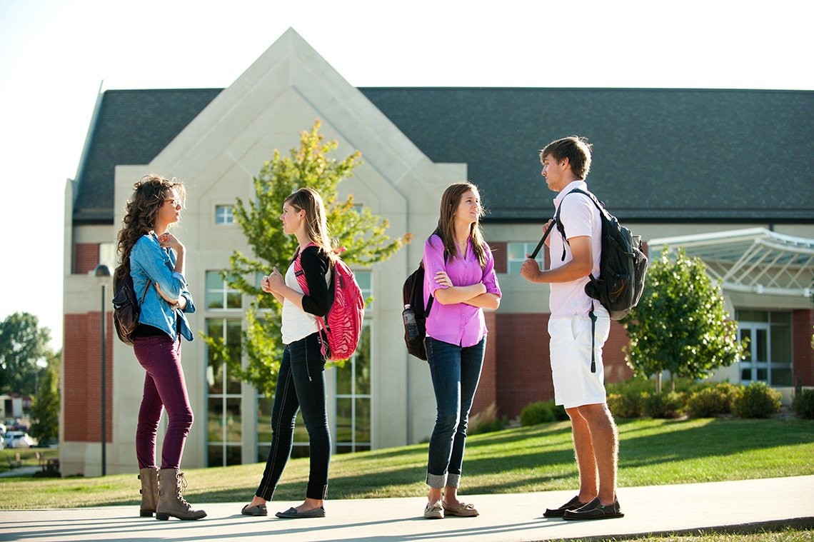 College students socializing outdoors at the Dordt College campus in Iowa.