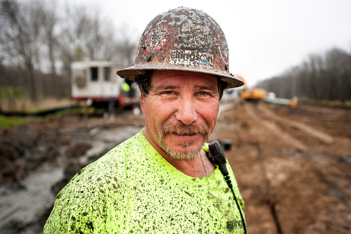 Industrial photography of pipeline worker with muddy hat and shirt