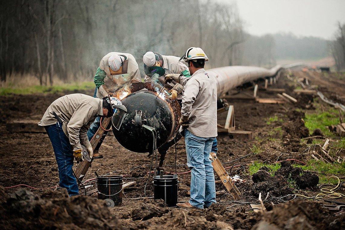 Industrial photography of welders working on a large oil pipeline.