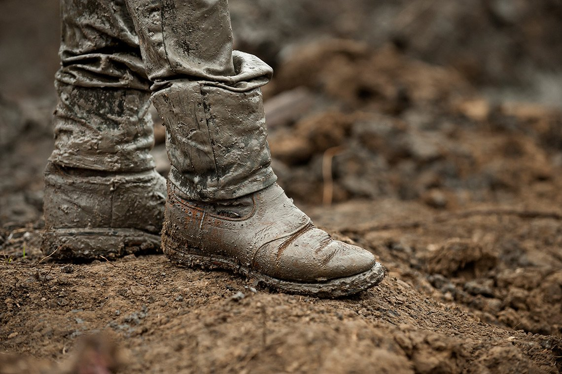 Industrial photography of the oil covered boots of a pipeline worker