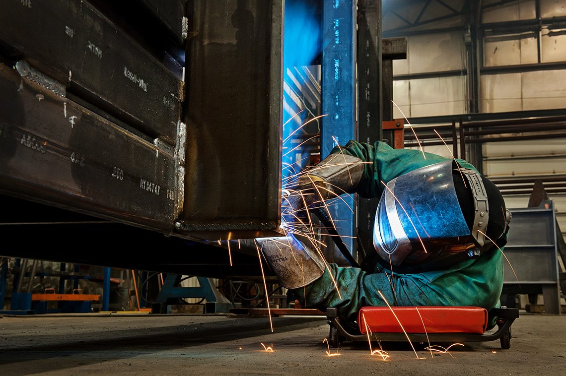 Industrial photography of a welder working on a large steel box