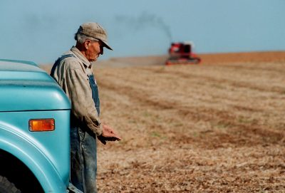 An old farmer leans against an old truck while his brother harvests soybeans in the background on a Minnesota farm