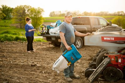 A man, his wife and baby on their Minnesota farm while planting soybeans.