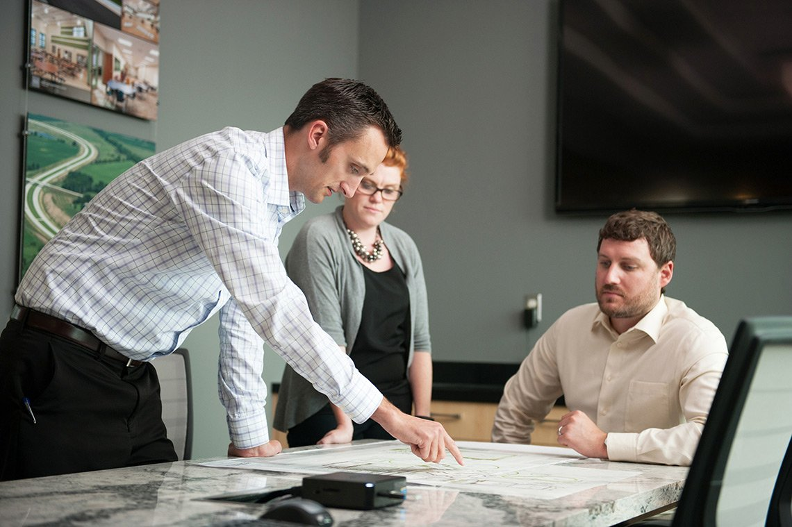 Architects and engineers go over blueprints in a conference room at ISG in Mpls MN