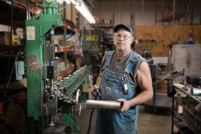 A man in overalls works in the shop area of Pure Humidifer in Minneapolis Minnesota