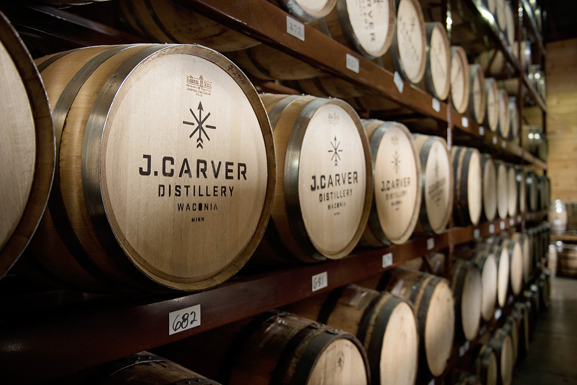 """Hospitality photo of rows of whiskey barrels stamped with """"J. Carver Distillery"""""""