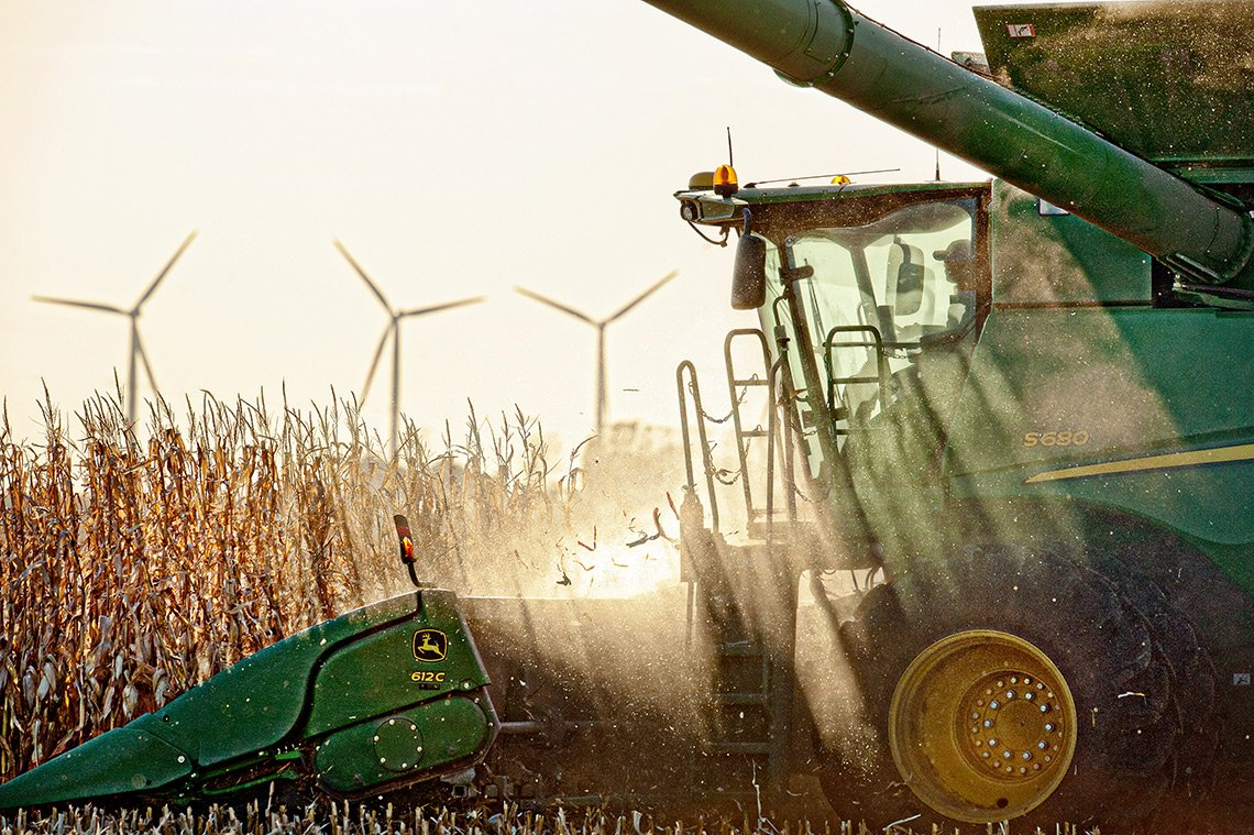 A John Deere combine goes through a corn field with three wind turbines in the background