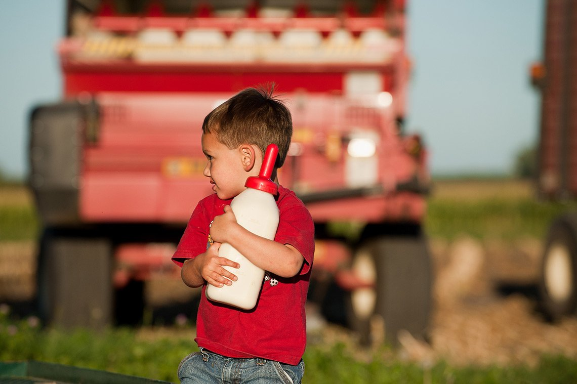 A young boy carrying a full milk bottle to feed the calves