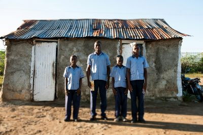 Four young brothers standing in front of their home in Fort Liberte Haiti