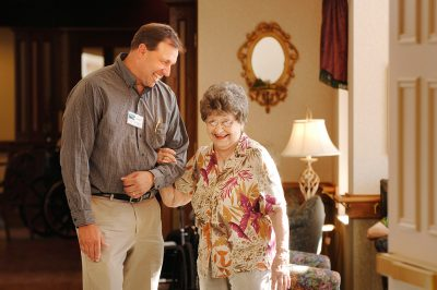 An employee helps an elderly woman at Thro retirement home in southern Minnesota.