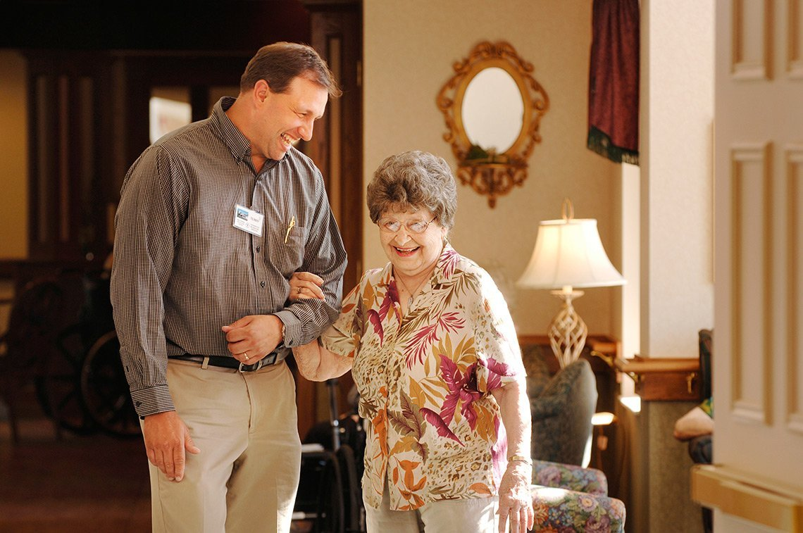 An employee helps an elderly woman at Thro retirement home in Minnesota.