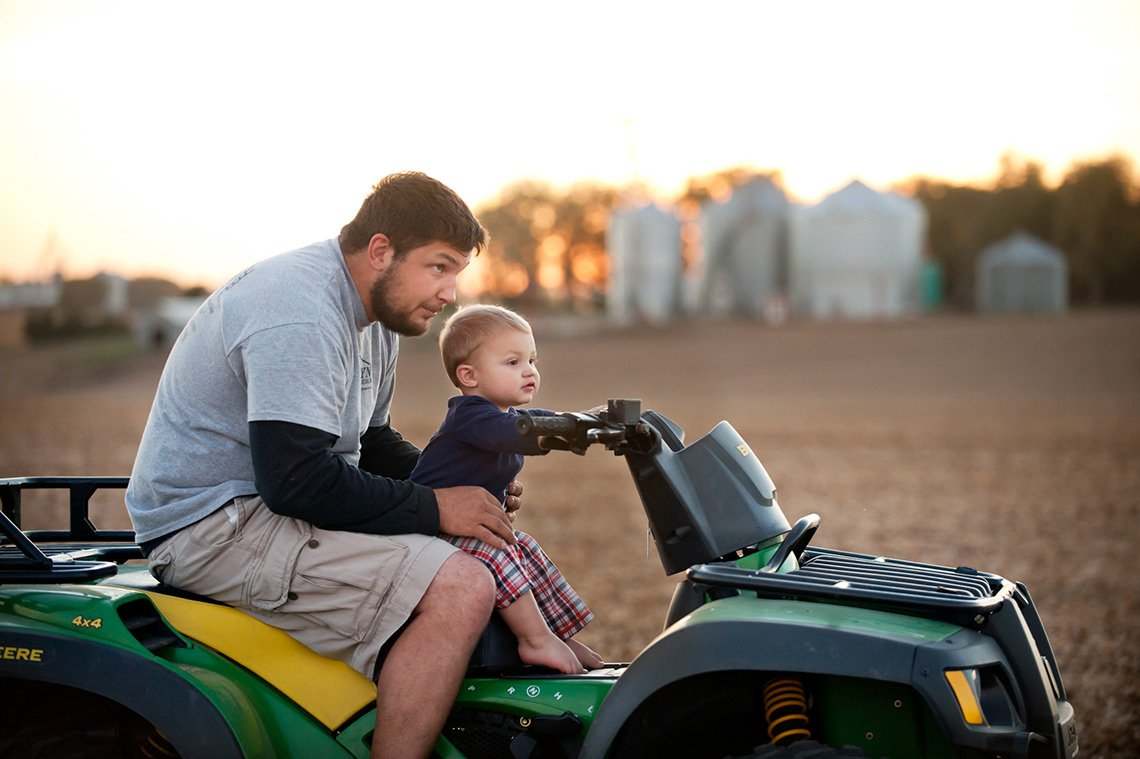 Agricultural photo of a father and son on an atv while out in the field.