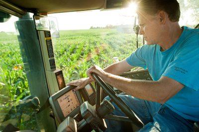 A farmer in his tractor in a corn field in Minnesota.