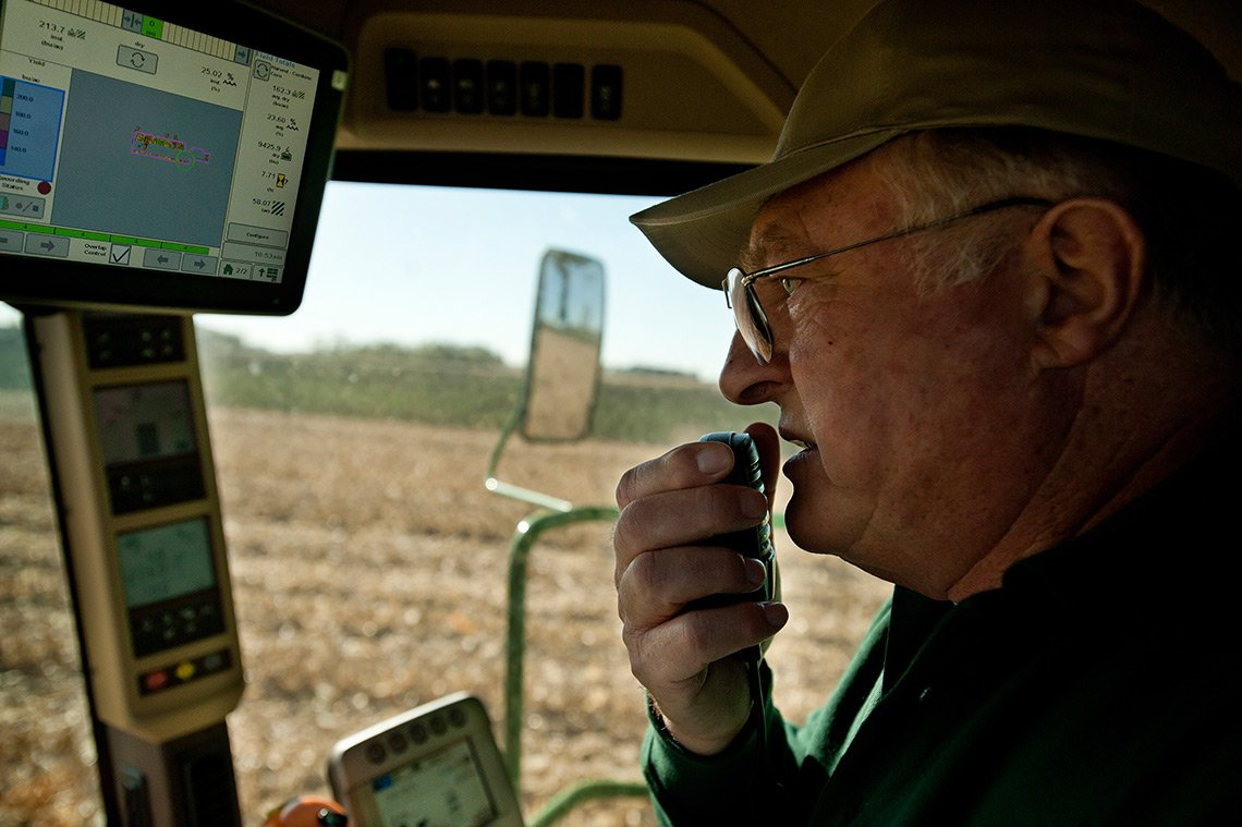 A farmer driving a combine while harvesting corn in southern Minnesota.