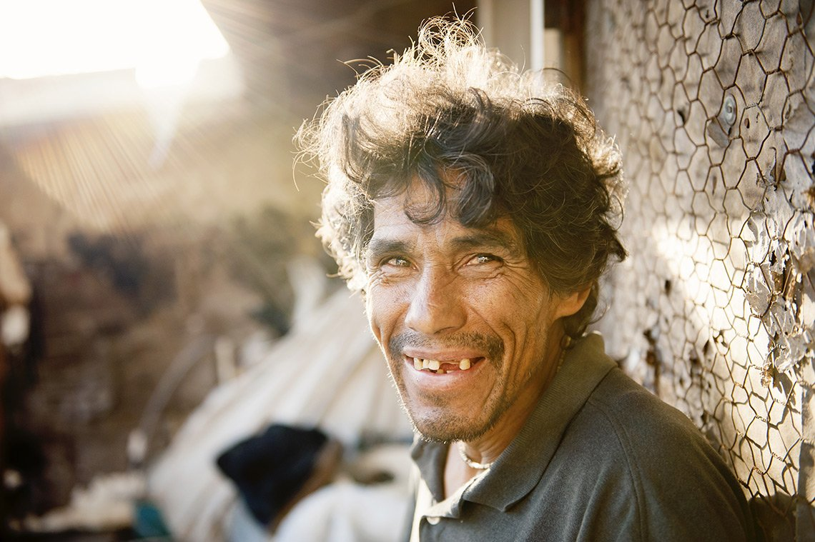 A homeless man missing a few teeth smiles in the afternoon sun in Tijuana