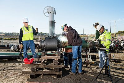 Industrial photography of welders working on a natural gas pipeline in Minnesota.