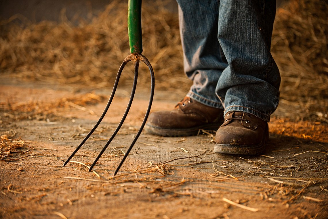 Farm life photo of boots and pitchfork of a farmer in Minnesota