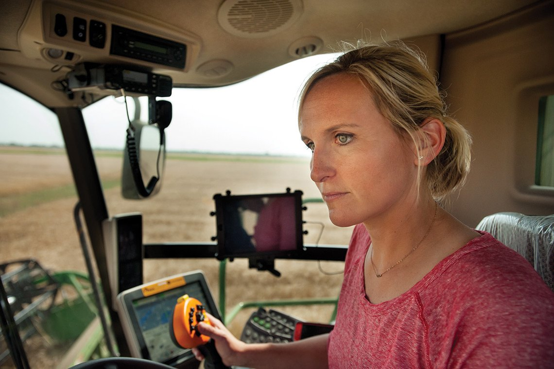 Agricultural photo of a female farmer driving a John Deere combine while harvesting wheat in ND.