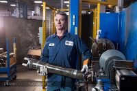 A worker with a steaming hot hydraulic cylinder at Aggressive Hydraulics in Minneapolis, Minnesota.