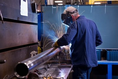 A welder at work in the shop area of Aggressive Hydraulics in Mpls MN