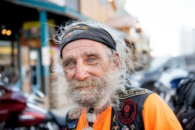 A 70-year-old Harley rider with long scraggly gray hair and beard and ice blue eyes outside of Wall Drug.