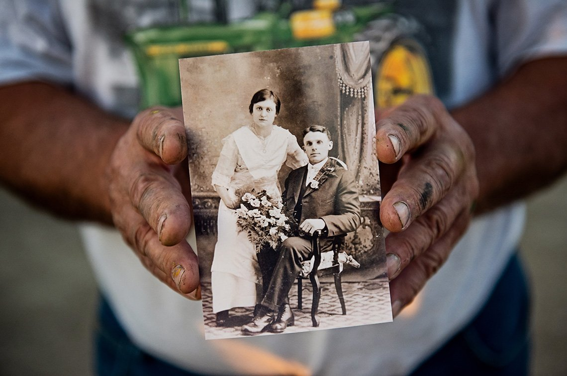 The dirty hands of a farmer holding an old family photo - Minnesota