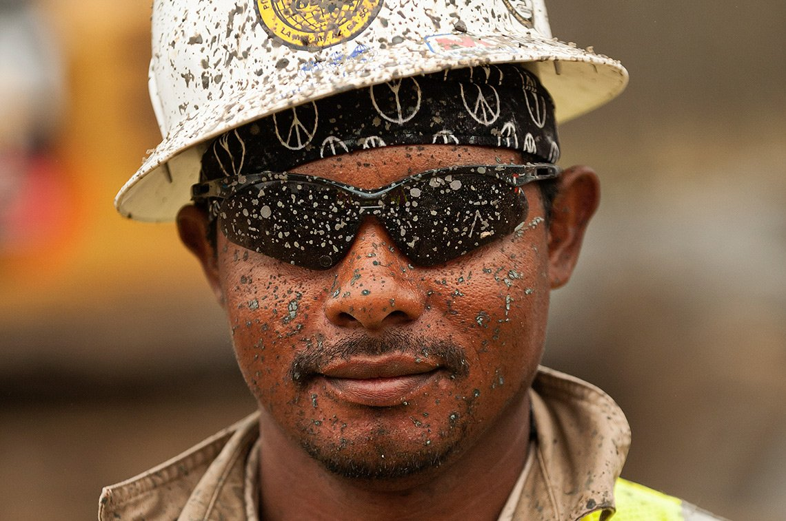 An industrial pipeline workers face covered in mud.