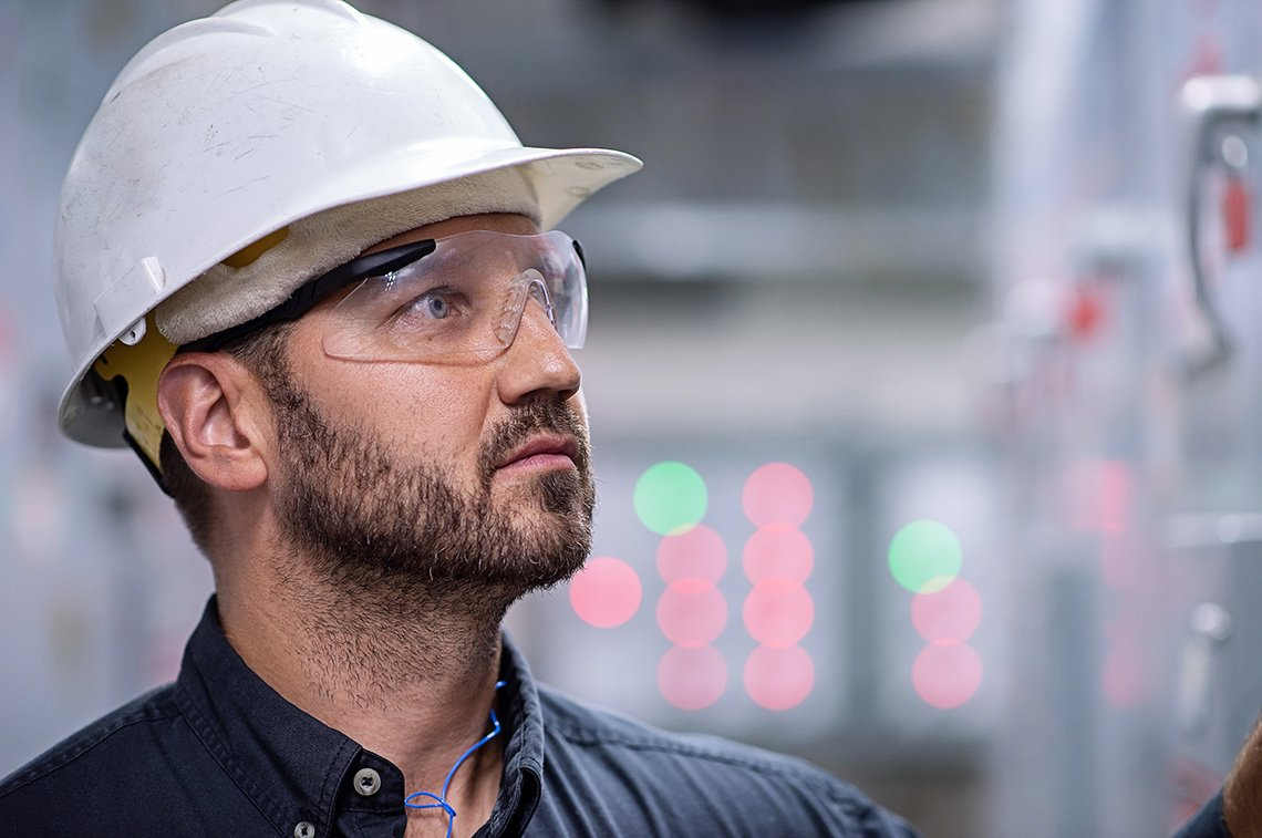 Industrial photography of a man's face with a hard hat and safety glasses in St Paul, Minnesota.