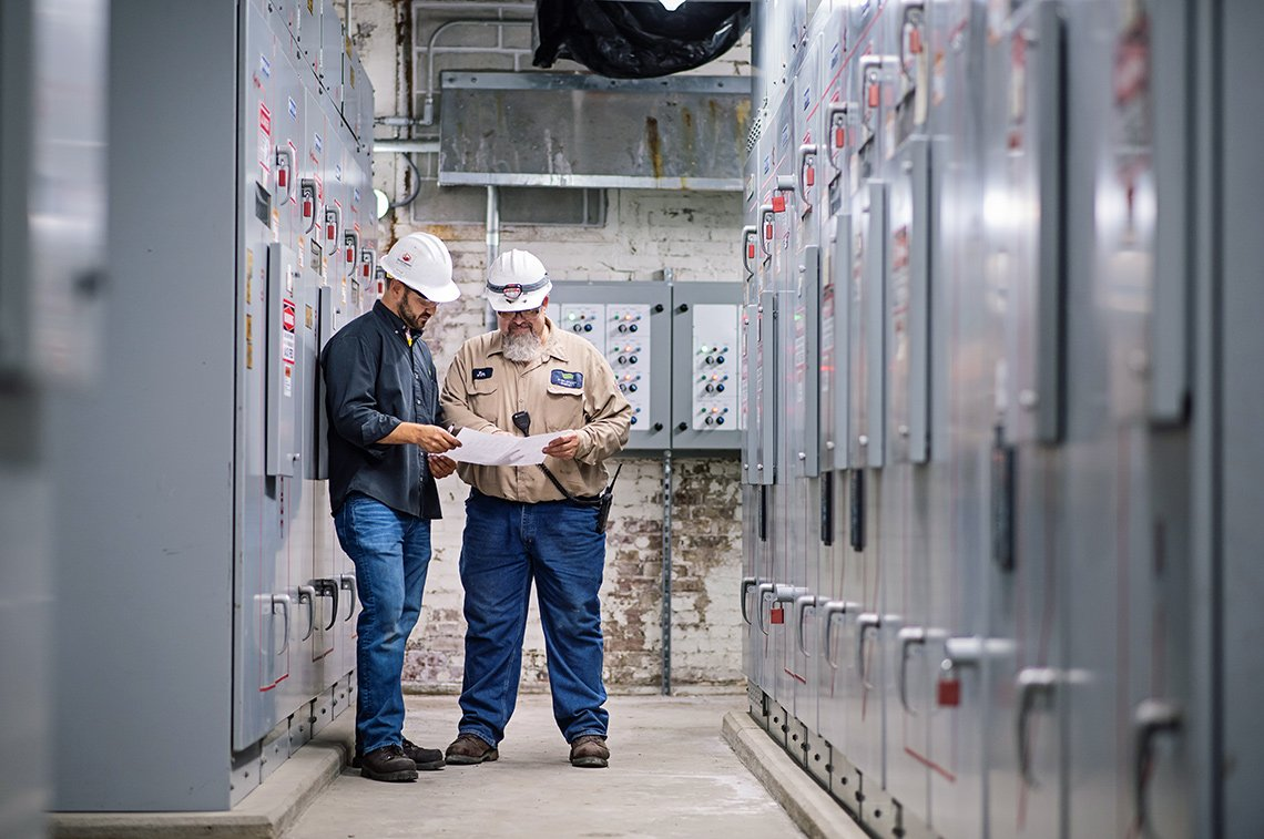 Industrial photography of two workers going over paperwork in the electrical area of a power station in St Paul, MN