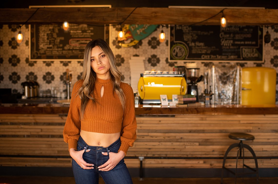 Woman standing in front of coffee bar fashion image
