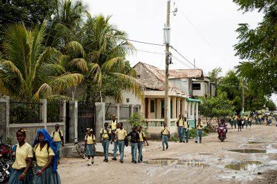 Numerous Haitian children in their school uniforms walk down the street after school.
