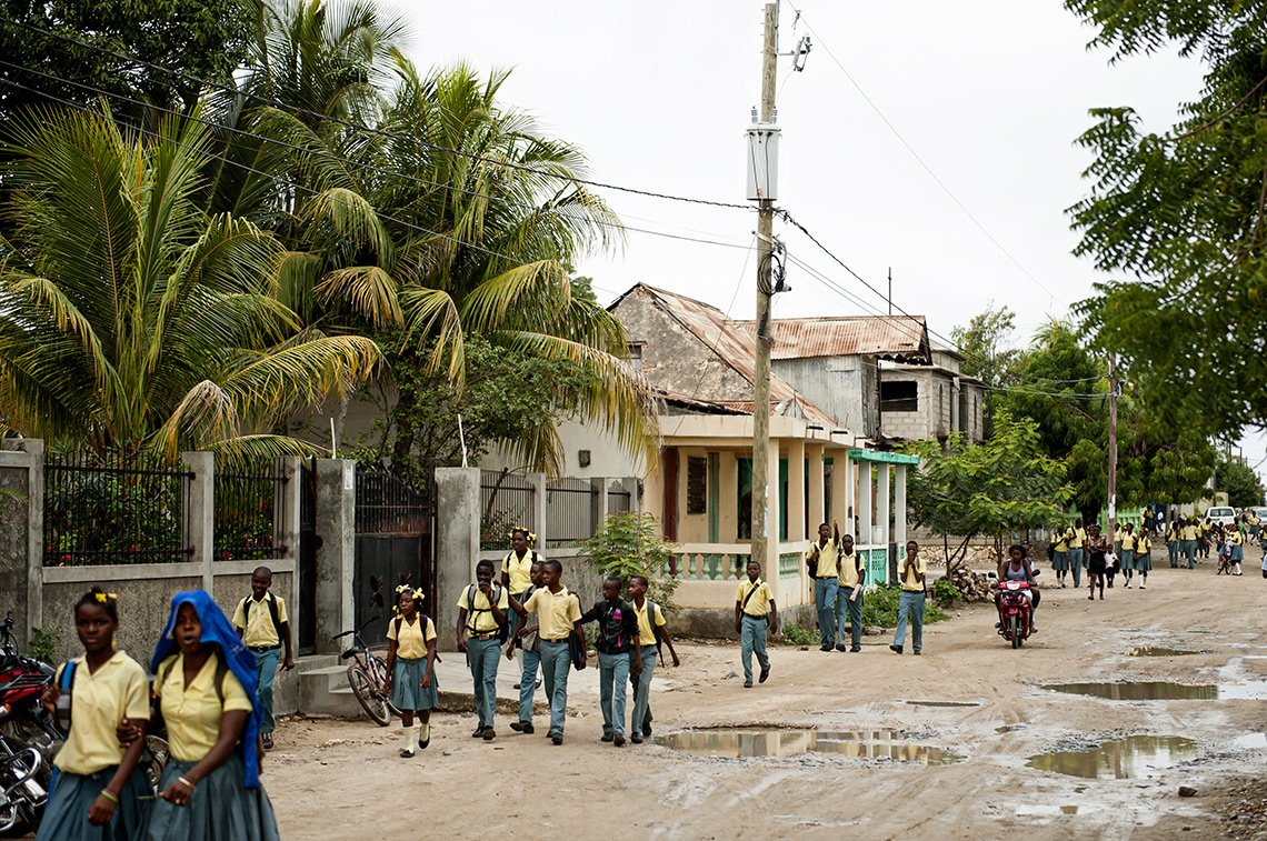 Numerous Haitian children in their school uniforms walk down the street after school.