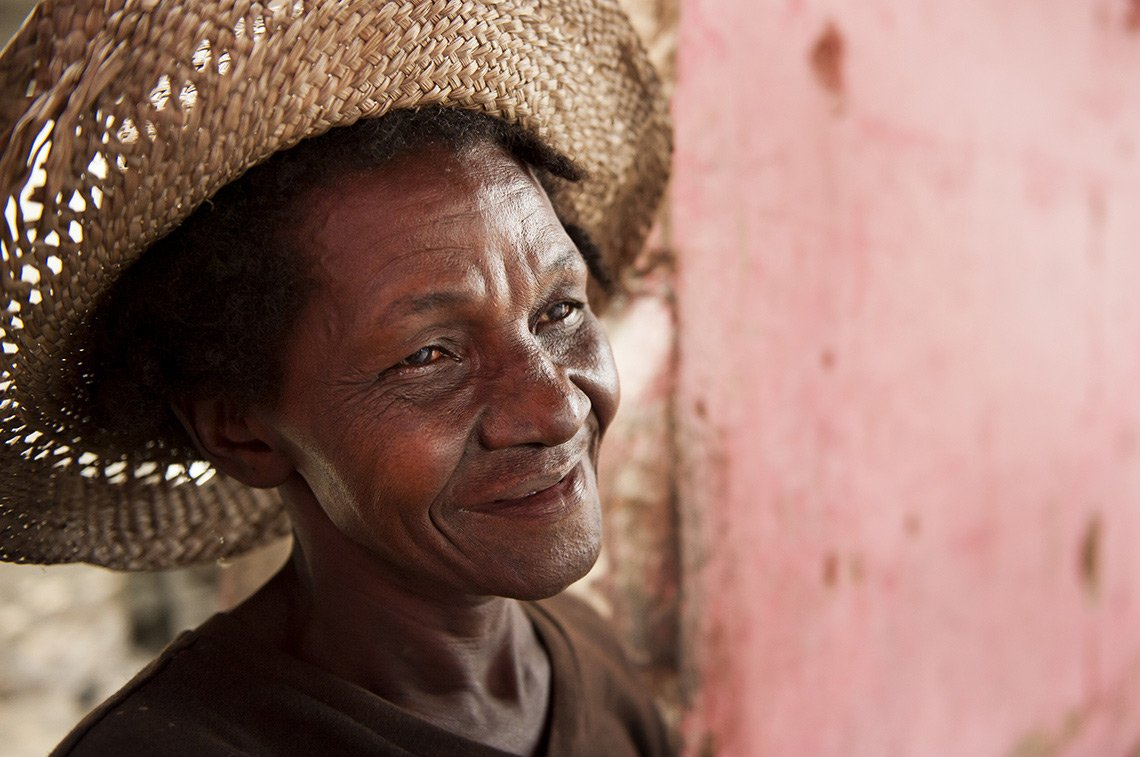 An older Haitian woman smiles in her straw hat.