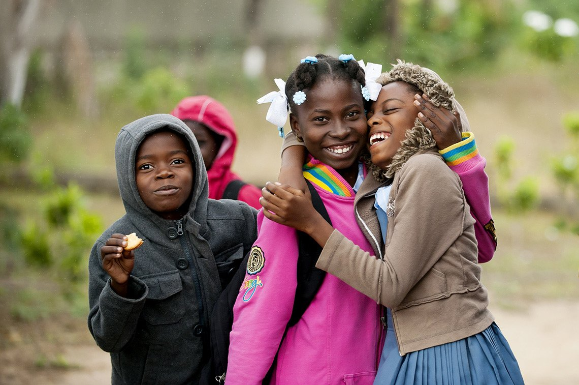Two girls hug and laugh outside of their private Catholic school in Haiti