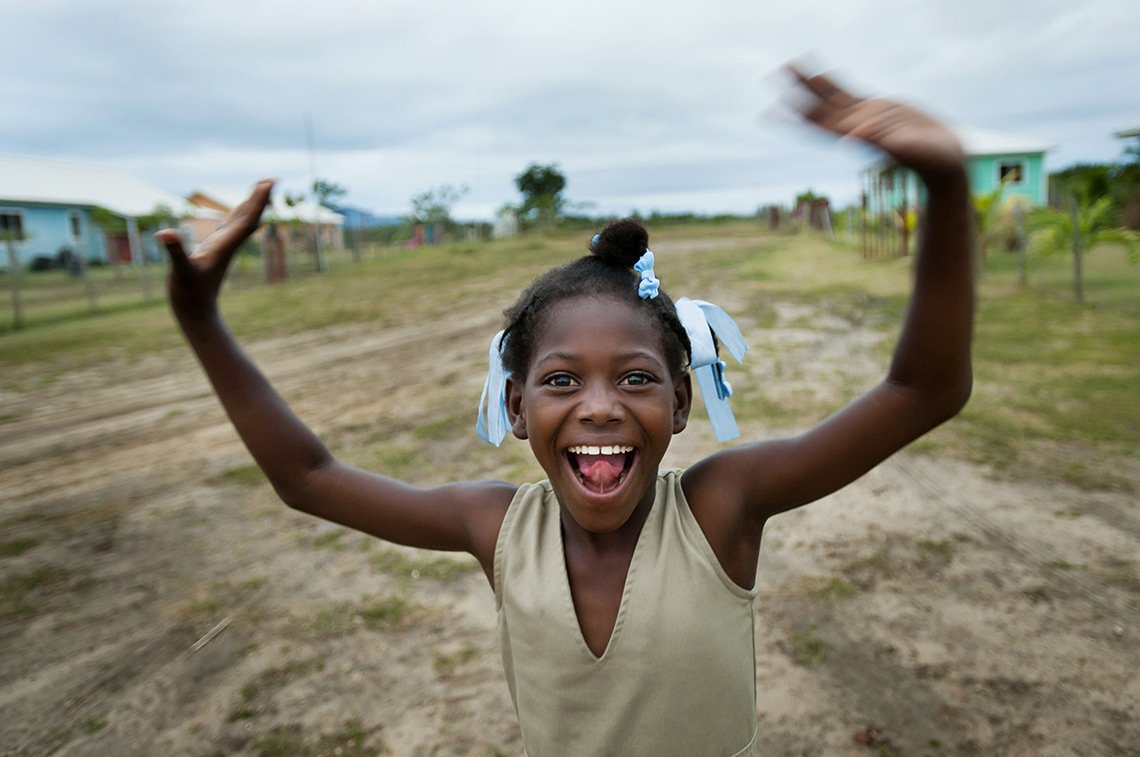 A young girl dances and laughs in Fort Liberte Haiti
