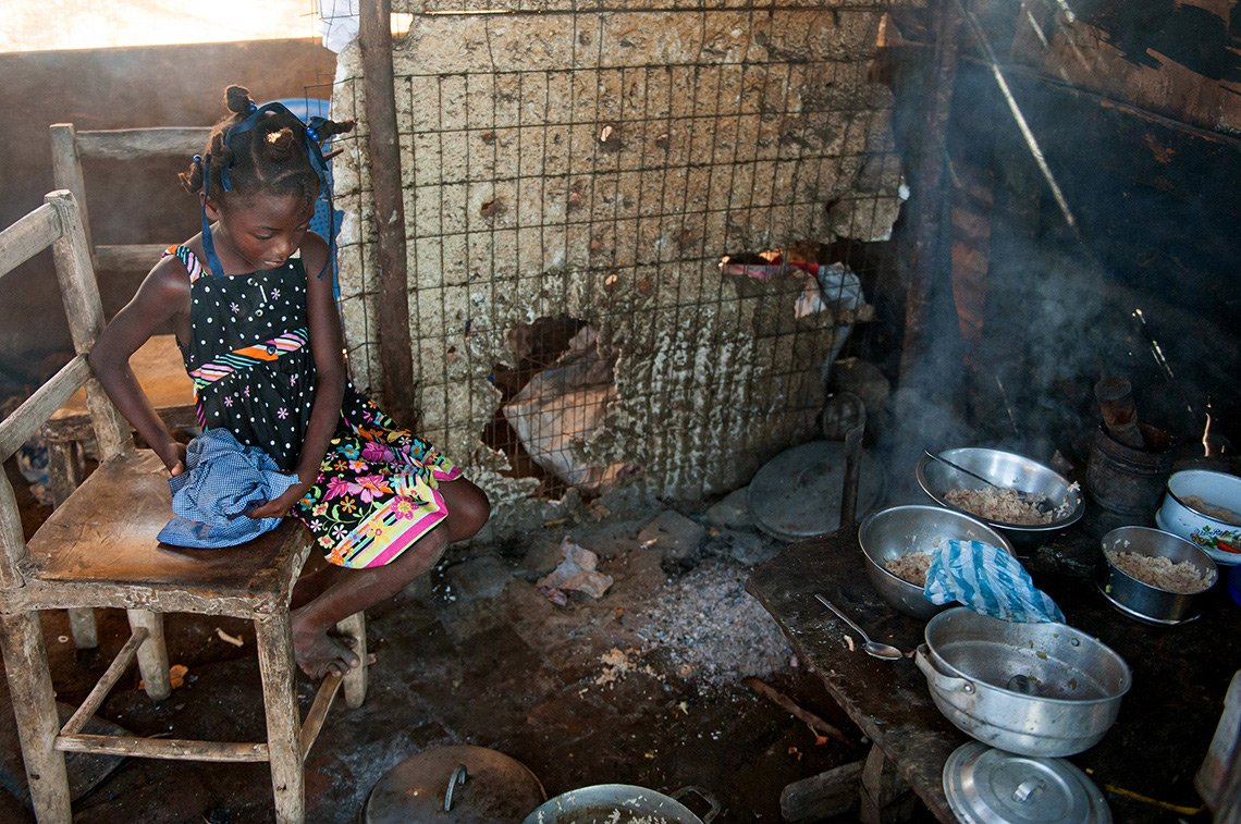 A young girl prepares food for her brothers in na make-shift Haitian kitchen