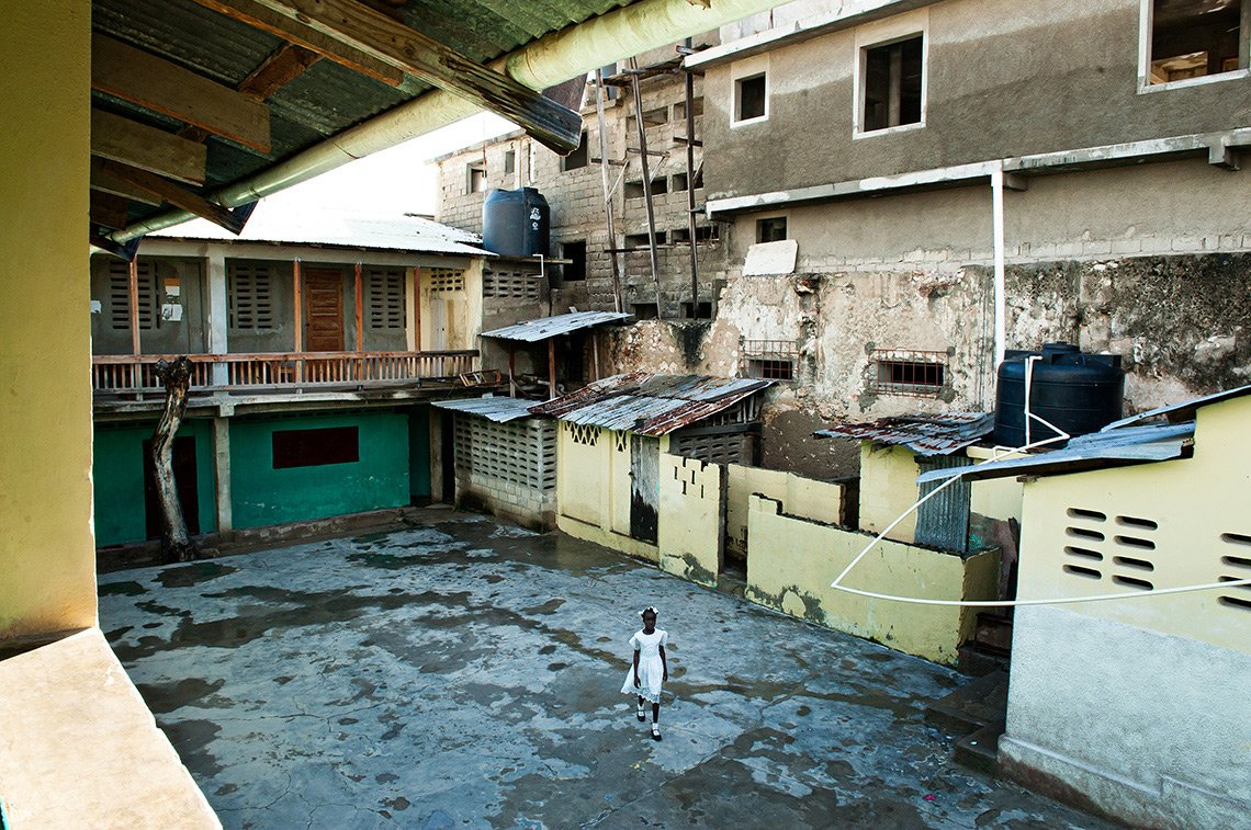 A young girl in a nice white dress walks through a rundown courtyard on her way to church