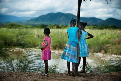 Three girls in bright colored dresses look out over the grassland and mountains in Haiti