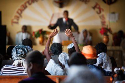 A woman raises her hands in the air during a church service in Haiti.
