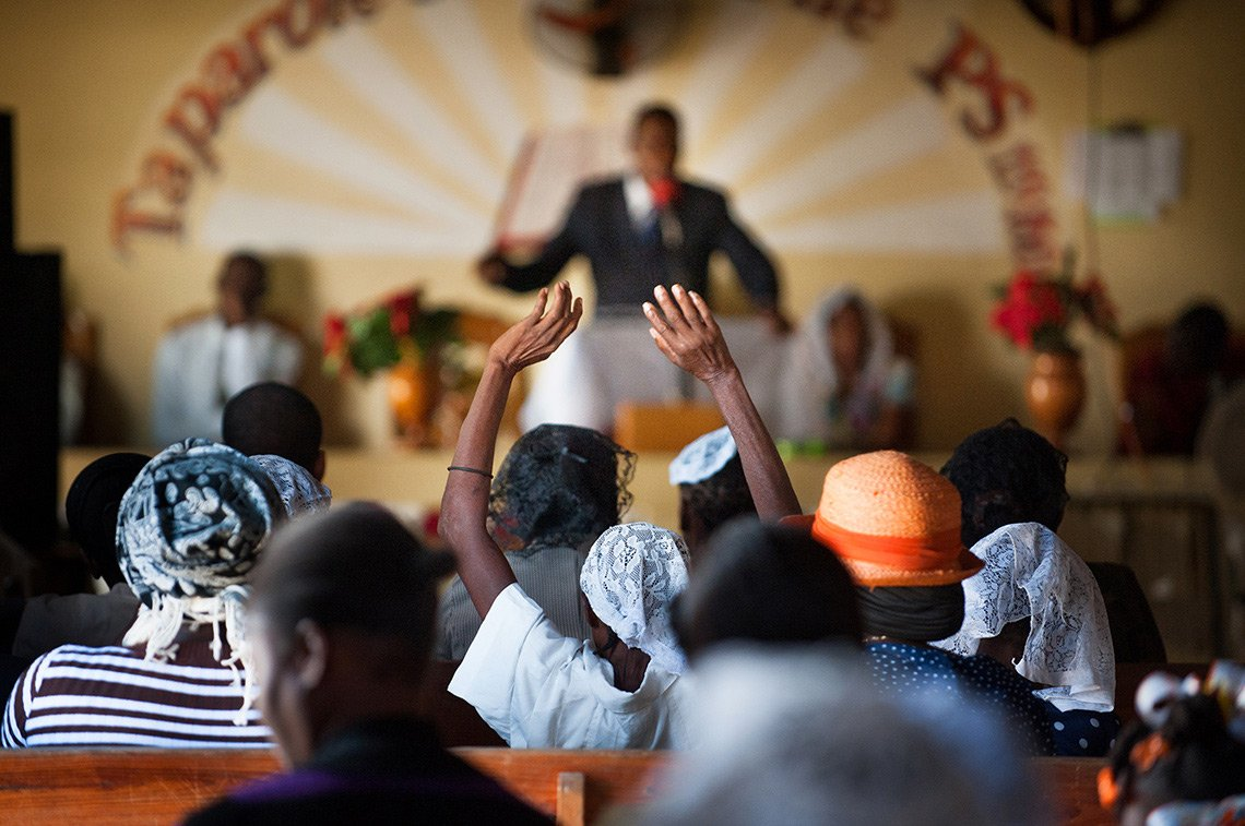 A woman raises her hands in the air during a church service in Haiti.