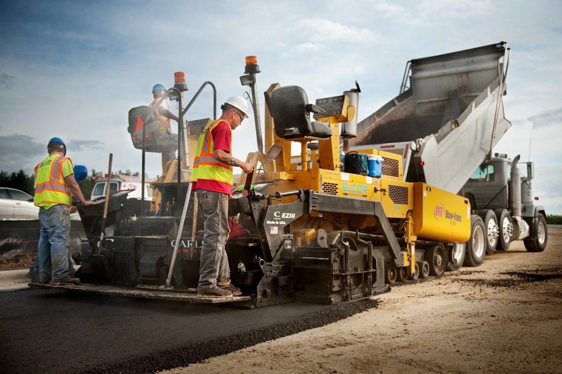 Industrial workers laying an asphalt road at a construction site.