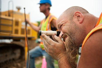 An Elcor Construction worker peers through a magnifying piece