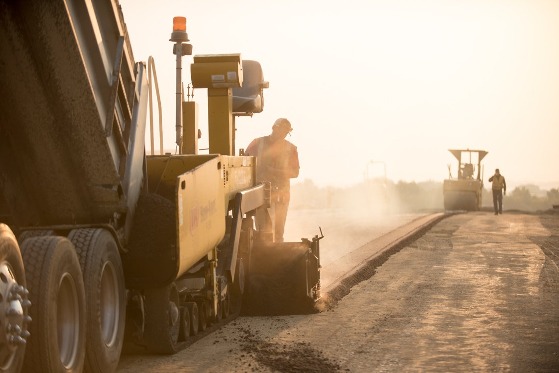 Workers laying asphalt while backlit from the early morning sun