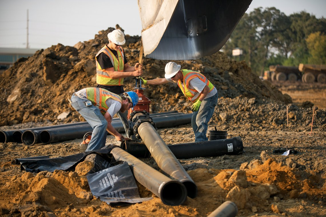 Industrial construction workers installing drain pipes at a residential construction site
