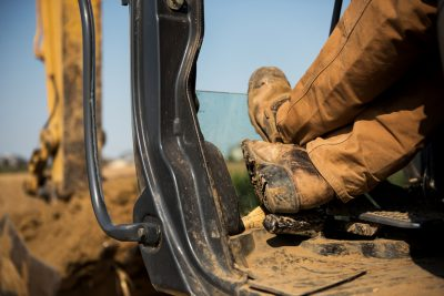 A workers legs and boots while operating a backhoe