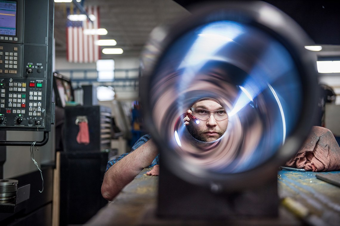 Industrial portrait of a worker looking down a steel pipe in Minneapolis MN