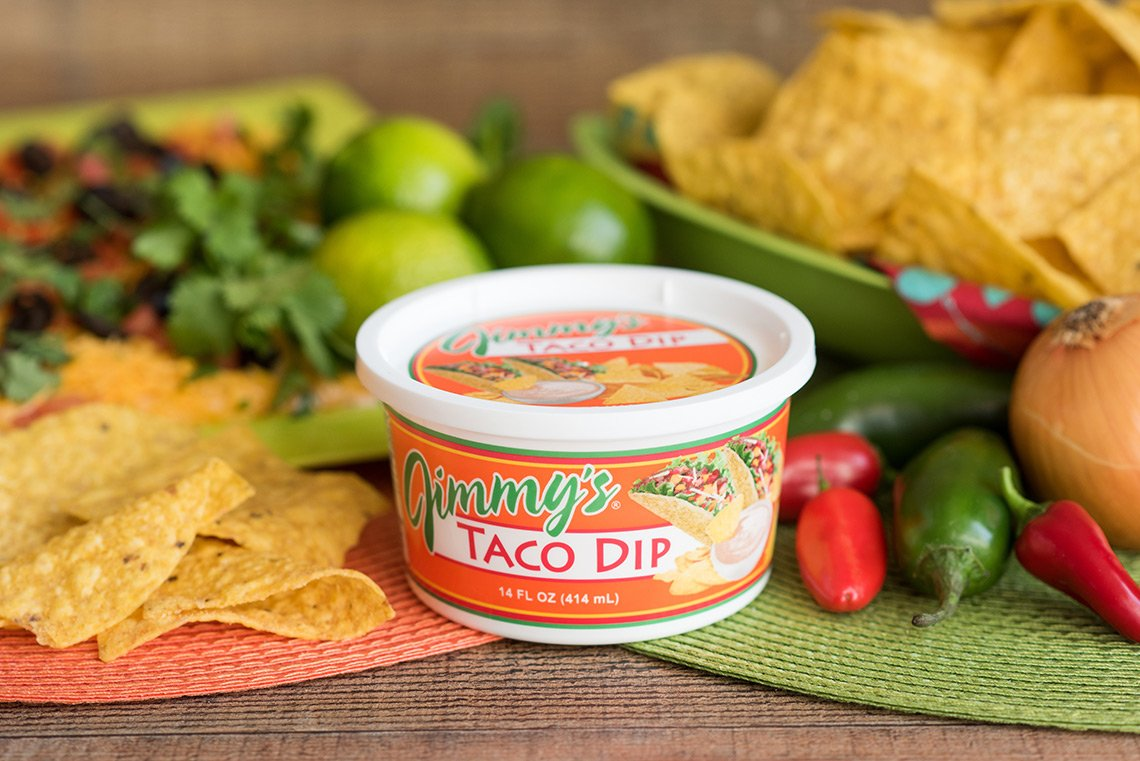 Product shoot of Jimmy's Taco Dip surrounded by chips, limes and peppers